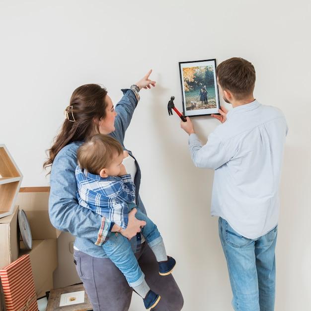 Vrouw die zijn zoon draagt die zijn echtgenoot leidt om het kader op muur te bevestigen Gratis Foto