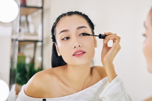 Vrouw die zwarte mascara toepast Premium Foto