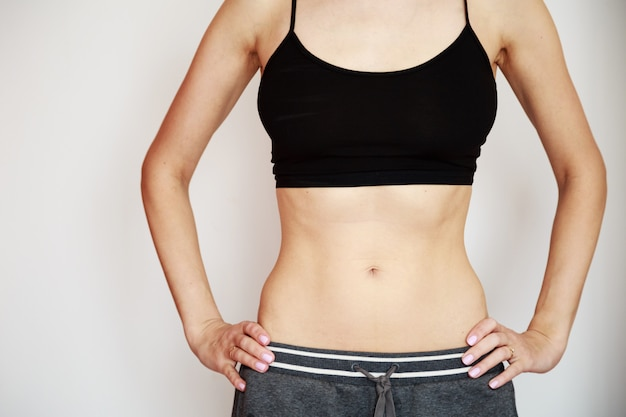 Vrouw die zwarte sportbeha en grijze broek met slank lichaam draagt Premium Foto