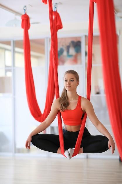 Vrouw doet beenspieren die zich uitstrekken met rode linten Gratis Foto