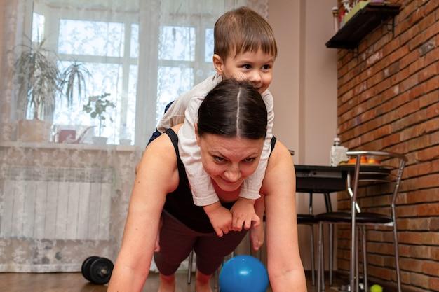 Vrouw doet fitness oefeningen met kinderen thuis Premium Foto