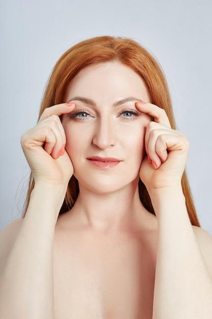 Vrouw doet gezichtsmassage, gymnastiek, massagelijnen en plastic mondogen en neus. massage Premium Foto