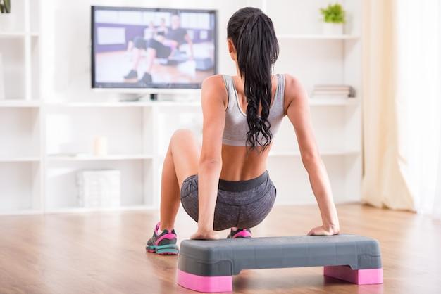 Vrouw doet huis oefeningen tijdens het kijken naar programma. Premium Foto