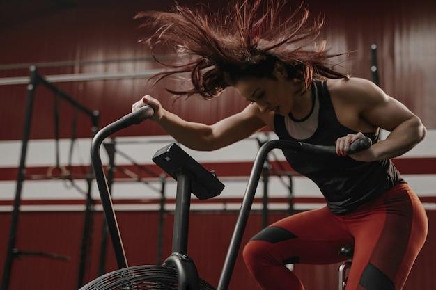 Vrouw doet intense cardiotraining op hometrainer Premium Foto