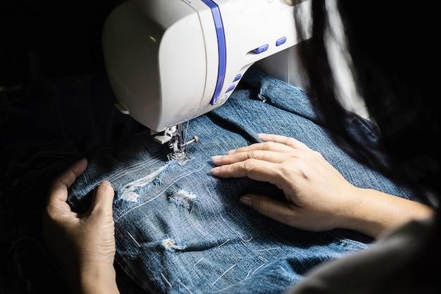 Vrouw doet jeans patchwork met behulp van naaimachine - thuis diy naaien concept Gratis Foto