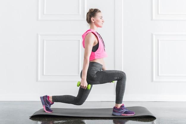 Vrouw doet oefeningen met halters Gratis Foto