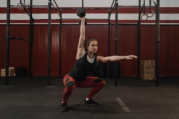 Vrouw doet overhead halter squats in de sportschool. vrouwelijke atleet training met gewichten oefenen Premium Foto