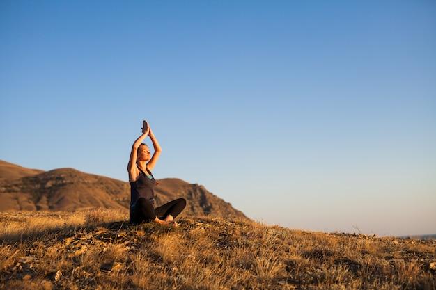 Vrouw doet yoga op de natuur buiten bij zonsopgang Premium Foto