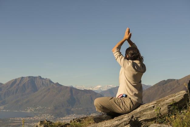 Vrouw doet yoga op de top van een berg op een zonnige dag in zwitserland Gratis Foto