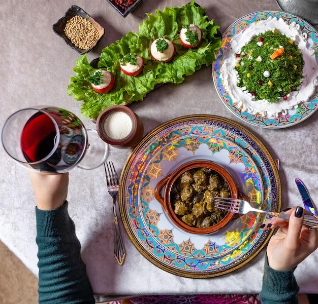 Vrouw dolma eten, met rode wijn bovenaanzicht Premium Foto
