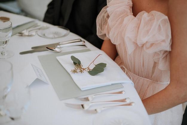 Vrouw draagt een jurk zit een bruiloft tafel met een servet en groen blad erop Gratis Foto