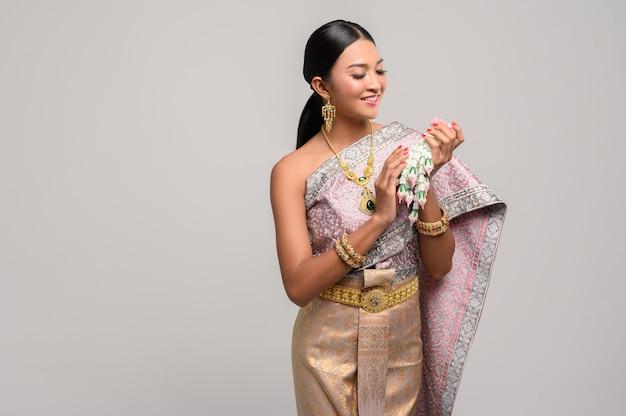 Vrouw draagt thaise kostuum en hand slingers van bloemen. Gratis Foto