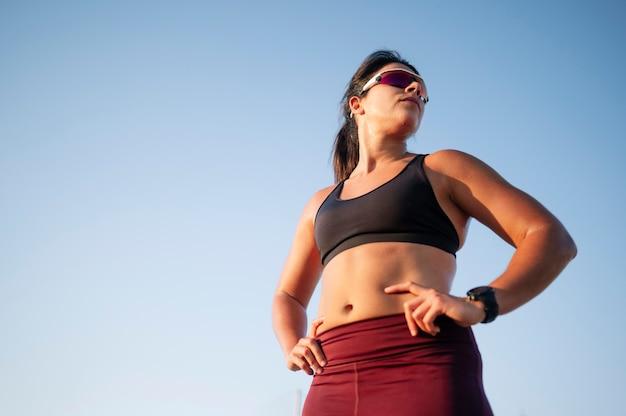 Vrouw draait op weg tegen blauwe hemel in stad tijdens zonnige dag Premium Foto