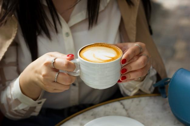 Vrouw drinken cappuccino-kop Gratis Foto
