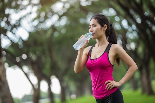 Vrouw drinkt water uit de oefening. Premium Foto
