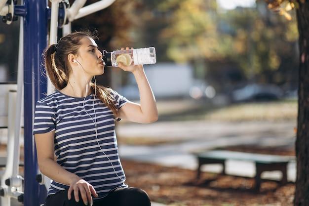 Vrouw drinkt water uit een shaker na de training. Premium Foto