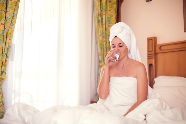 Vrouw drinkt zoet water in de ochtend. mensen, gezondheidszorg, lifestyle concept Premium Foto