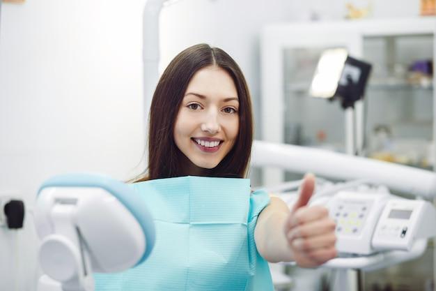 Vrouw duimen opdagen bij een receptie bij de tandarts Gratis Foto