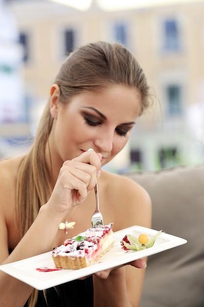 Vrouw eet een taart Gratis Foto