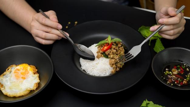 Vrouw eet roergebakken gehakt varkensvlees met basilicum (pad ka prao), gebakken ei en chili vissaus in thais restaurant Premium Foto