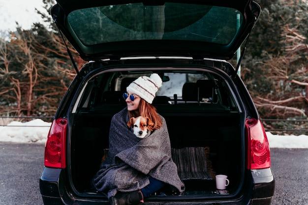 Vrouw en de leuke hond die van hefboomrussell in openlucht bij de berg in de auto genieten van. reizen concept. winter seizoen Premium Foto