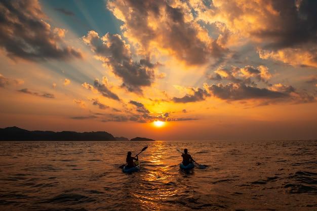 Vrouw en een man zeilen met kano's dicht bij elkaar bij zonsondergang Gratis Foto
