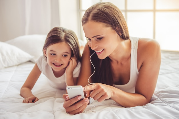 Vrouw en haar dochter in oortelefoons luisteren naar muziek Premium Foto