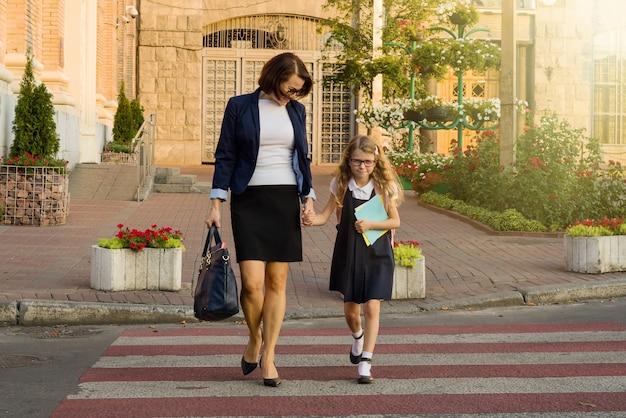 Vrouw en kind jonge schoolmeisje hand in hand, bij zebrapad Premium Foto