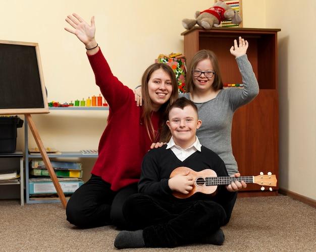 Vrouw en kinderen met het syndroom van down glimlach en golf Premium Foto