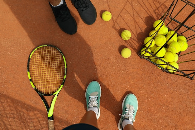 Vrouw en man benen in sneakers op gravel met tennisballen en racket Premium Foto