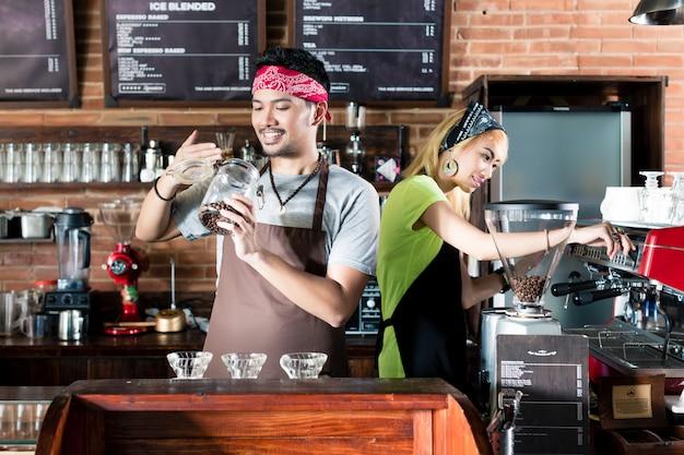 Vrouw en man die in aziatische koffie koffie voorbereiden Premium Foto