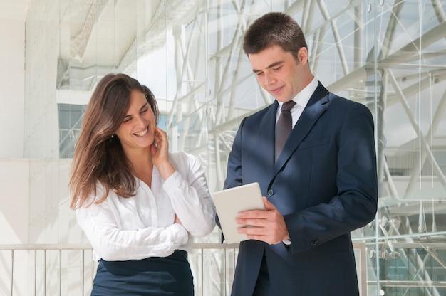 Vrouw en man die zich in gang, man bevinden die gegevens over tablet tonen Gratis Foto