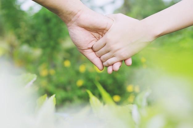 Vrouw en man hand in hand, gelukkige paar liefde in de tuin. Premium Foto