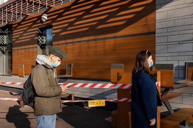 Vrouw en man op straat met masker Gratis Foto