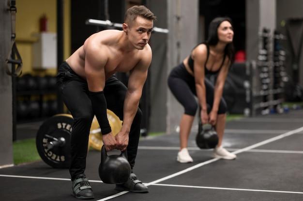 Vrouw en man opleiding met gewichten Gratis Foto