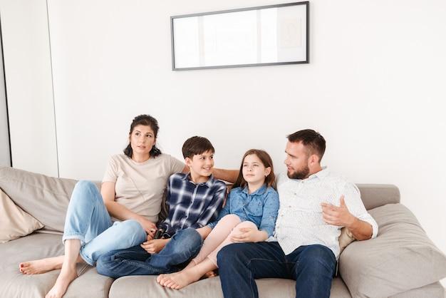Vrouw en man zittend op de bank samen, met kinderen meisje en jongen in de huiskamer Premium Foto