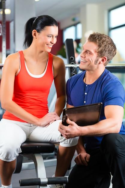 Vrouw en persoonlijke trainer in fitness gym Premium Foto