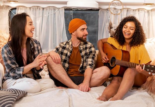 Vrouw en vrienden gitaarspelen Gratis Foto