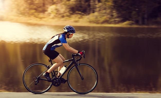 Vrouw fietsen racefiets buiten oefening Premium Foto