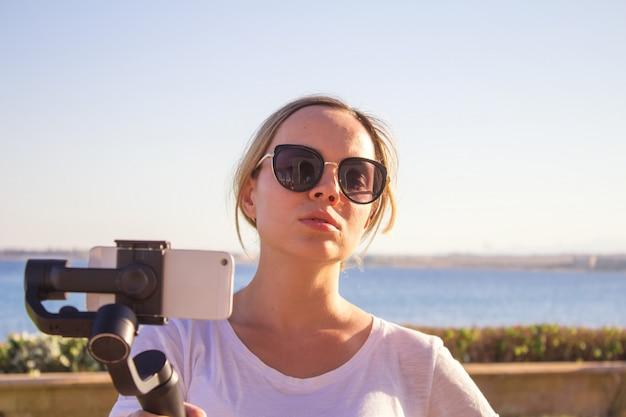 Vrouw filmen zonsondergang op reizen, video blogger video met gimbal en mobiele telefoon maken Premium Foto