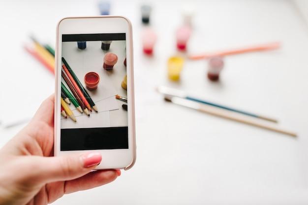 Vrouw fotograferen met mobiele smartphone camera werkruimte van kunstenaar voor het tekenen van kleurpotloden, aquarel, verf, penseel, schetsboek, papier geïsoleerd op een wit oppervlak Premium Foto