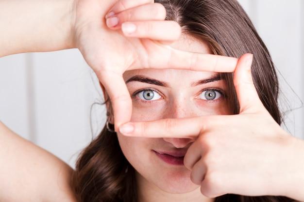 Vrouw frame ogen met vingers Gratis Foto
