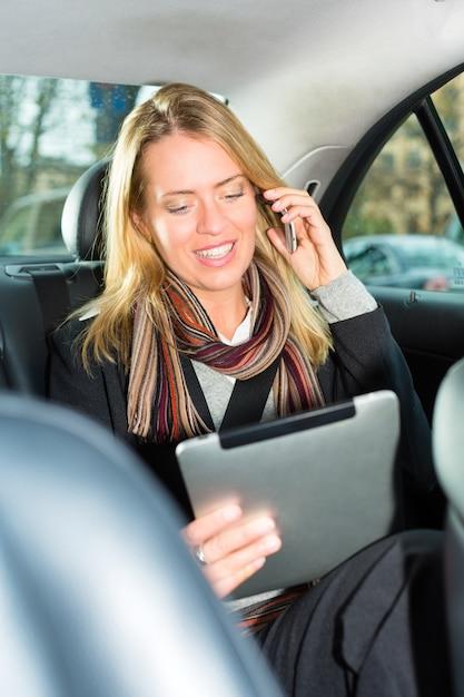 Vrouw gaat met de taxi, ze is aan de telefoon Premium Foto