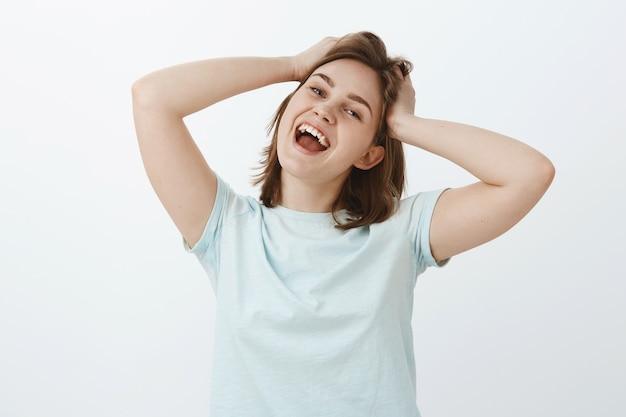 Vrouw gaat winkelen met een opgewonden en tevreden gevoel dat eindelijk salaris ontvangt. portret van zorgeloos blij aantrekkelijk meisje aanraken en verpesten haar breed glimlachend van positieve emoties Gratis Foto