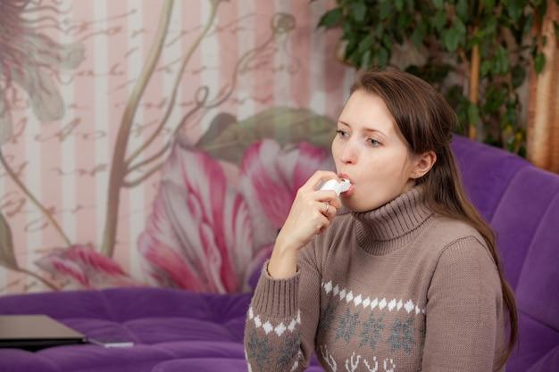 Vrouw gebruikt een inhalator tijdens een astma-aanval Premium Foto