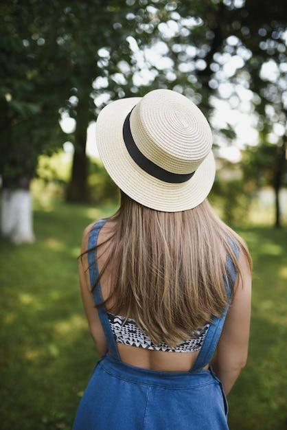 Vrouw, gekleed in blauwe jurk en witte hoed in het park Premium Foto