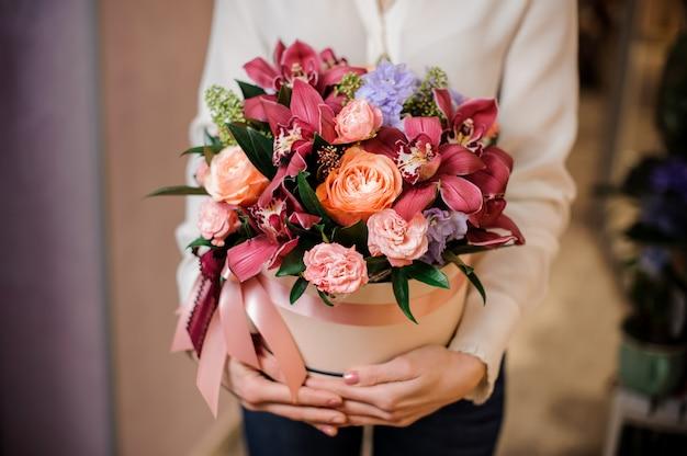 Vrouw gekleed in een witte blouse met een doos bloemen Premium Foto