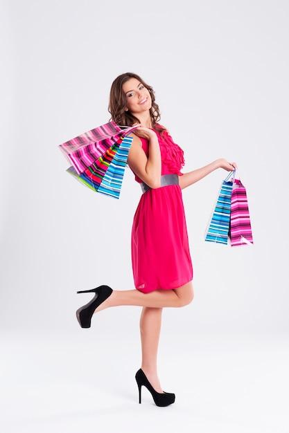 Vrouw, gekleed in roze jurk met boodschappentassen Gratis Foto