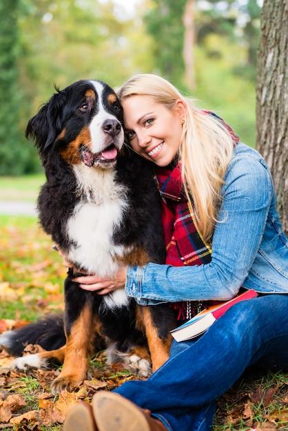 Vrouw geknuffel met hond buiten in park Premium Foto