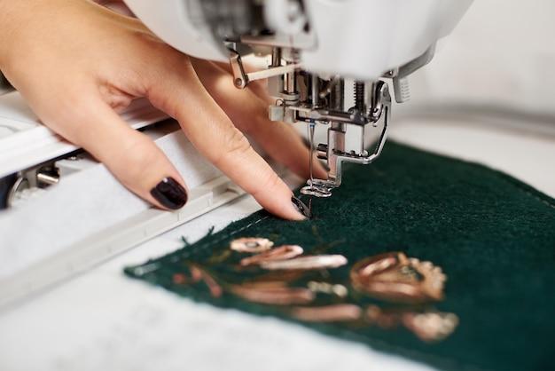 Vrouw gemanicuurde hand bezig met naaimachine Premium Foto